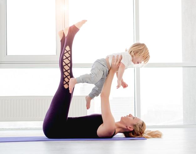 Семейная тренировка йоги дома. блондинка мать упражнения и держит сына в вытянутых руках над собой