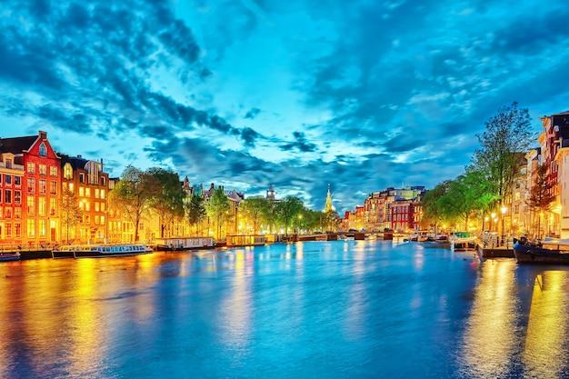 Знаменитая река амстел и ночной вид на красивый город амстердам. нидерланды