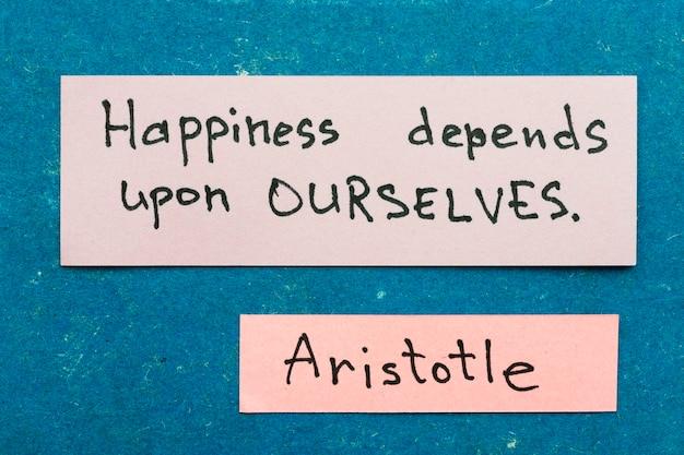 유명한 고대 그리스 철학자 아리스토텔레스는 행복에 대한 빈티지 판지 판에 스티커 메모와 함께 해석을 인용합니다.