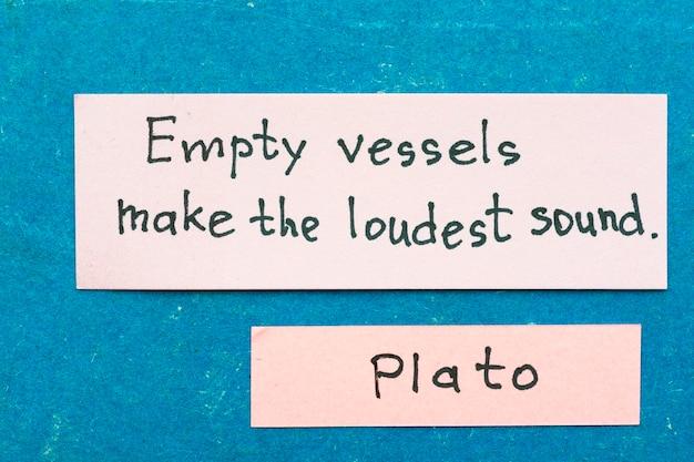 유명한 고대 그리스 철학자 플라톤은 옹알이에 대한 빈티지 판지 판에 스티커 메모와 함께 해석을 인용합니다.