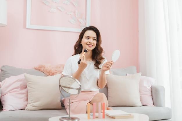 有名な美しいアジアの女性プロの美容ブロガーがブログのメイクアップチュートリアル録画ビデオをやっています。