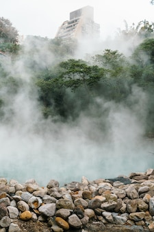 The famous beitou thermal valley in beitou park, boiling steam from hot spring floating through the trees in taipei city, taiwan.