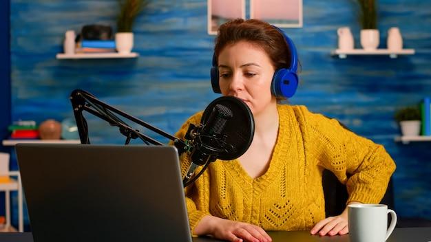 有名なブロガーがノートパソコンを開いて、現代のスタジオでマイク録音ポッドキャストを読み上げてコンテンツを作成