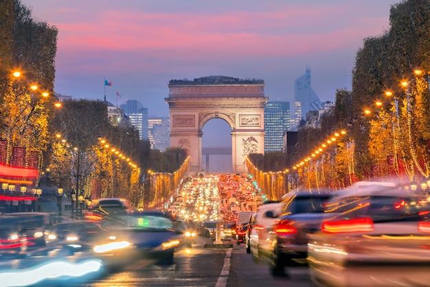 Знаменитые елисейские поля и триумфальная арка в сумерках в париже, франция