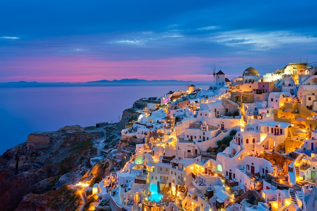 Famous greek iconic selfie spot tourist destination oia village with traditional white houses and windmills in santorini island in the evening blue hour, greece