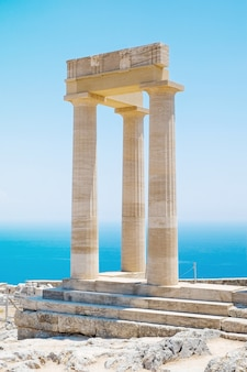 ギリシャのリンドスアクロポリスロードスアテナ寺院の澄んだ青い空と海を背景にした有名なギリシャ神殿の柱