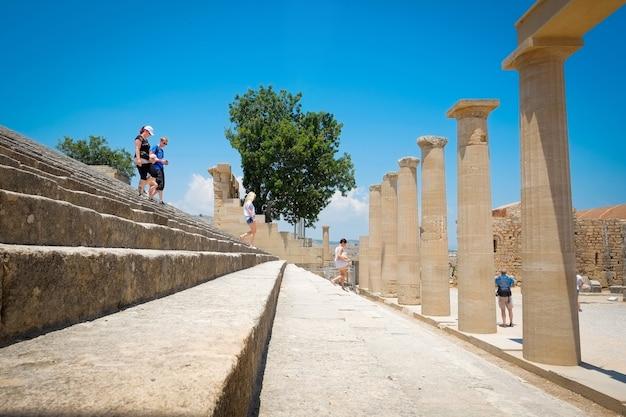 ギリシャのリンドスアクロポリスロードスアテナ寺院の澄んだ青い空を背景にした有名なギリシャ神殿の柱と石の階段