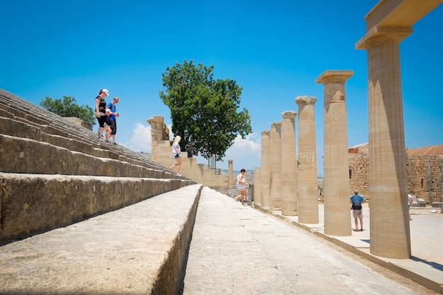 Famous greek temple pillar and stone staircase against clear blue sky in lindos acropolis rhodes athena temple, greece