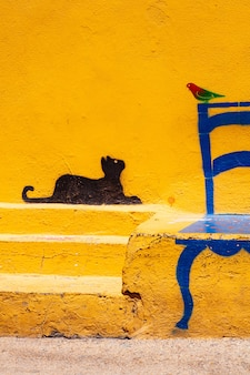 Famous illustration on linosa's wall of a cat looking at a bird sitting on a chair, pelagie island. sicily