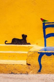 ペラージェ島の椅子に座っている鳥を見ている猫のリノザ島の壁の有名なイラスト。シチリア島