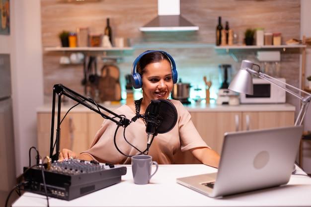 プロのギアを使用してホームスタジオでオンラインショーをホストしている有名なインフルエンサー。オンラインショーオンエアプロダクションインターネット放送ホストストリーミングライブコンテンツレコーディングデジタルソーシャルメディアコミュニケーション