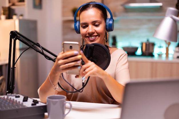 彼女のソーシャルメディアでのライブ中に彼女の電話でファンからのメッセージを読んでいる有名なインフルエンサー