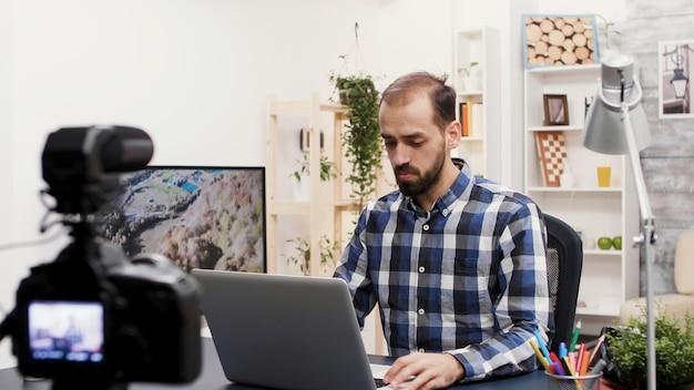 Известный влиятельный человек говорит и рассматривает ноутбук. создатель креативного контента. запись нового видеоблога.