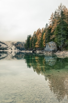 Famous lago di braies lake in italy on a foggy weather with beautiful reflections in autumn season