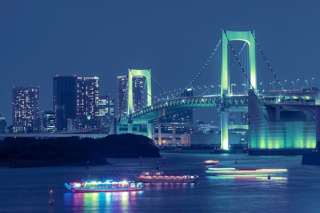 有名なランドマーク、美しい夜のイルミネーションと伝統的な日本のボートで湾の水に架かる東京レインボーブリッジ