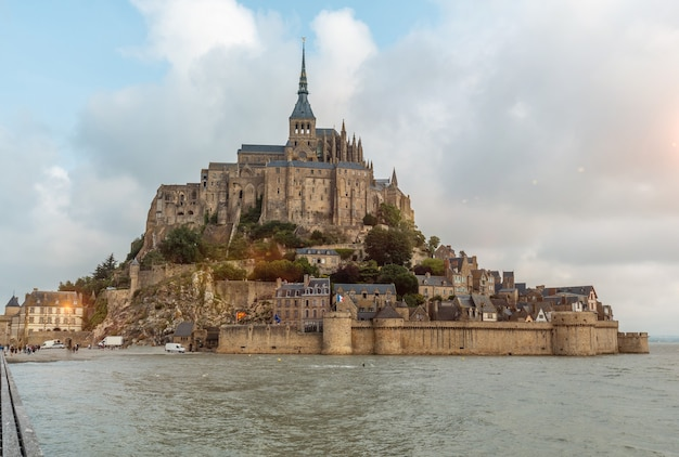 The famous mont saint-michel abbey at sunrise at high tide in the manche department, normandy region, france