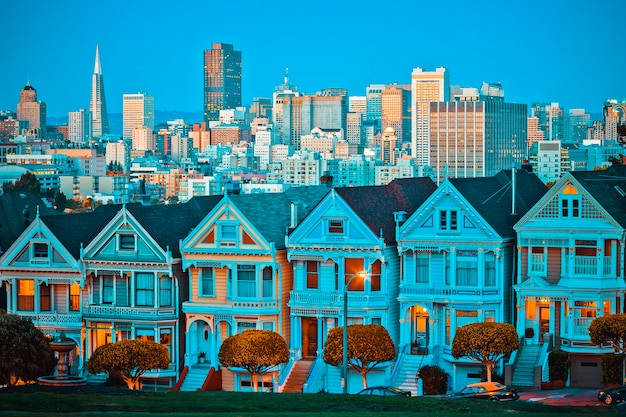 カリフォルニア州サンフランシスコの有名なペインテッドレディースは、夕日と高層ビルを背景に輝きます。