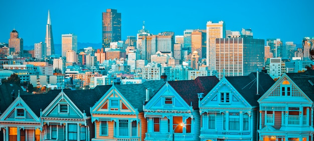 Famous painted ladies of san francisco, california sit glowing amid the backdrop of a sunset and skyscrapers.