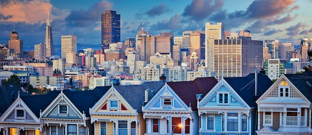 Famous painted ladies of san francisco, california sit glowing in sunset and skyscrapers.