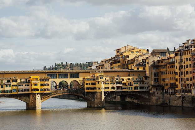 Знаменитый мост понте веккьо с рекой арно во флоренции, италия.