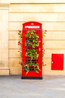 Famous red telephone booth in london with leaves