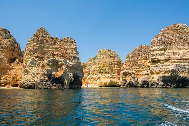Знаменитые скалы в море, океане, лагуше в португалии. популярное место для летних путешествий и знаменитый пляж на побережье алгарве.