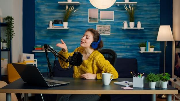 ポッドキャストのホームスタジオからカメラでフォロワーにキスする有名なvlogger。オンエアオンライン制作インターネット放送ショーホストストリーミングライブコンテンツ、デジタルソーシャルメディア通信の記録
