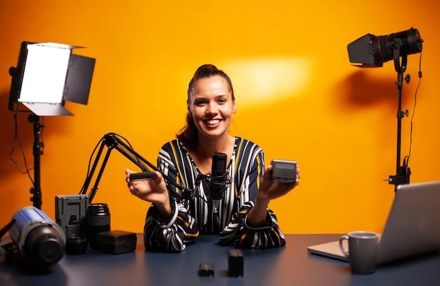 전문 축전지에 대한 동영상을 녹화하면서 웃고 있는 유명 동영상 블로거