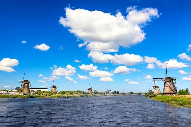 Знаменитые ветряные мельницы в деревне киндердейк в нидерландах. красочный весенний сельский пейзаж. всемирное наследие юнеско и известный туристический объект.