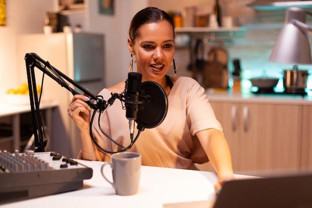 ソーシャルメディアのポッドキャストを録音しながらプロのマイクを持っている有名な女性。オンエアのオンライン制作インターネット放送番組のホストは、ライブコンテンツをストリーミングし、デジタルソーシャルメディアを録画します。