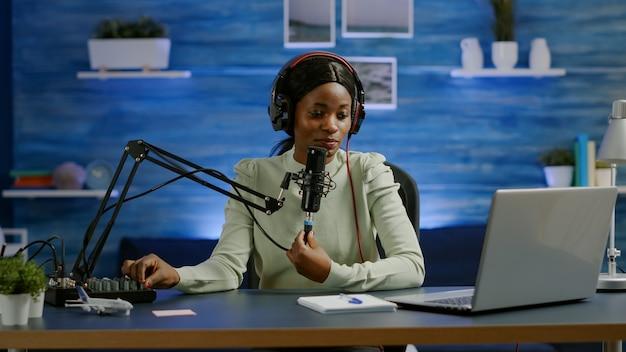 동영상 블로그에 팟캐스트 마이크를 사용하여 구독자를 위한 동영상 블로그를 녹화하는 유명한 젊은 아프리카 여성. 온에어 온라인 제작 인터넷 방송 쇼 호스트 스트리밍 라이브 콘텐츠 소셜 미디어