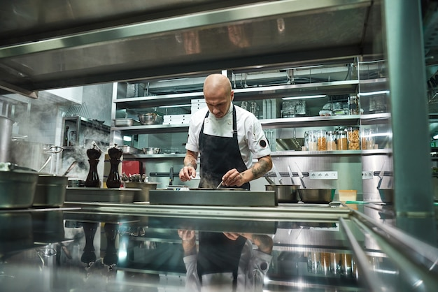Famous young chef in black apron working at his modern restaurant kitchen