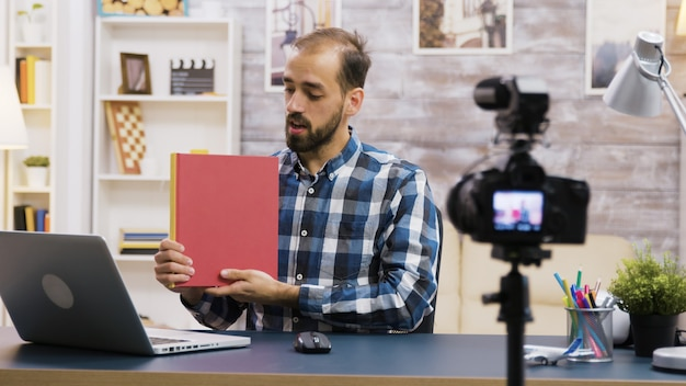 Famous young vlogger recording a review of a book for subscribers. vlogger lifestyle.