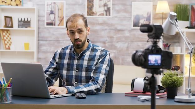 팟캐스트에서 구독자와 이야기하면서 노트북으로 타이핑하는 유명한 젊은 블로거. 크리에이티브 콘텐츠 크리에이터.
