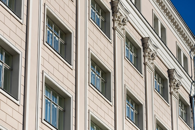 The fañade is a classic white stone building with rounded windows, column and a wrought-iron balcony. soviet architecture