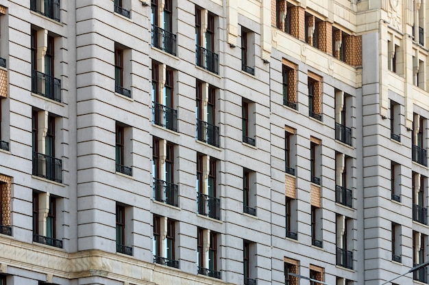 The fañade is a classic white stone building with  a wrought-iron balcony. soviet architecture