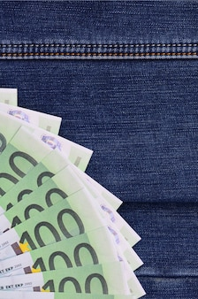 The fan of a lot of euro bills is on a dark denim surface. background image