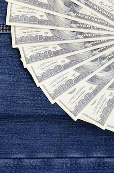 The fan of a lot of us dollars is on a dark denim surface. background image