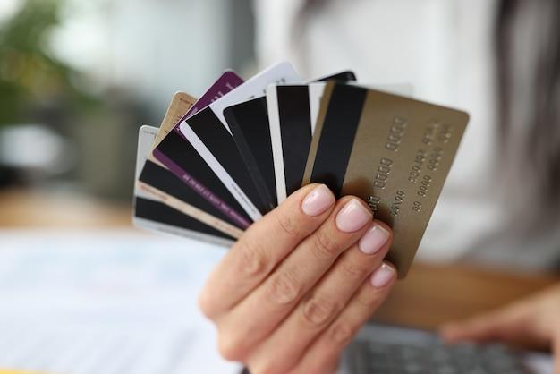 プラスチック製の銀行カードのファンは女性の手にあります。収益性の高い銀行はコンセプトを提供します