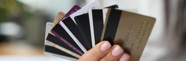 Поклонник пластиковых банковских карт в руках женщин. прибыльный банк предлагает концепцию