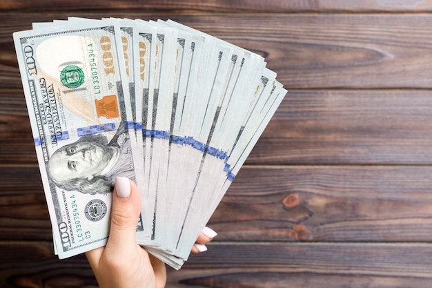 Fan of one hundred dollar bills in female hand on wooden surface