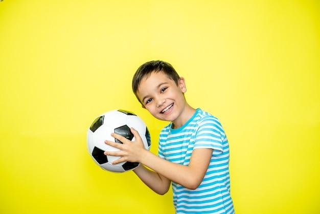 팬 스포츠 소년 선수는 행복한 미소 웃음 쇼 엄지손가락을 축하하는 줄무늬 티셔츠에 축구공을 들고