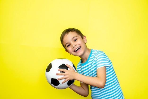 팬 스포츠 소년 선수는 행복한 미소 웃음 쇼를 축하하는 줄무늬 티셔츠에 축구공을 들고