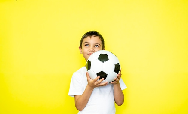 팬 스포츠 소년 선수는 행복한 미소 웃음 쇼 엄지손가락을 축하하는 흰색 티셔츠에 축구공을 들고