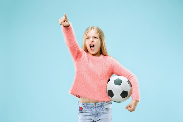 青い背景で隔離のサッカーボールを保持しているファンスポーツティーンプレーヤー
