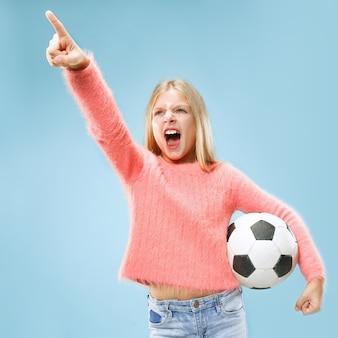 青いスペースで隔離のサッカーボールを保持しているファンスポーツティーンプレーヤー