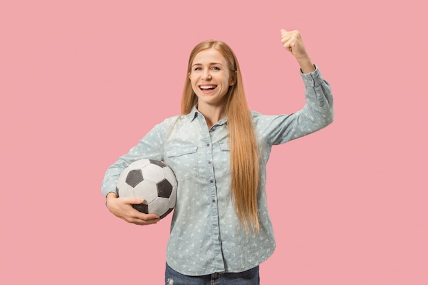 Fan sport woman player holding soccer ball isolated on pink background
