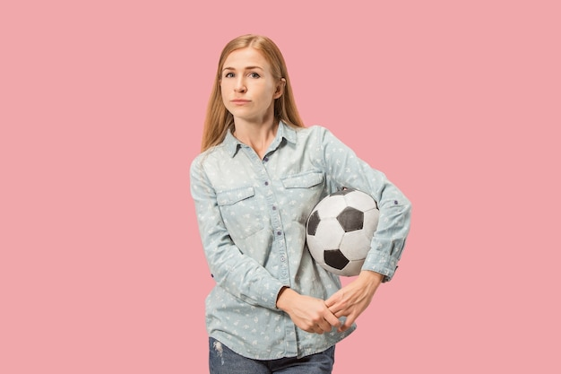 Fan sport woman player holding soccer ball isolated on pink studio background
