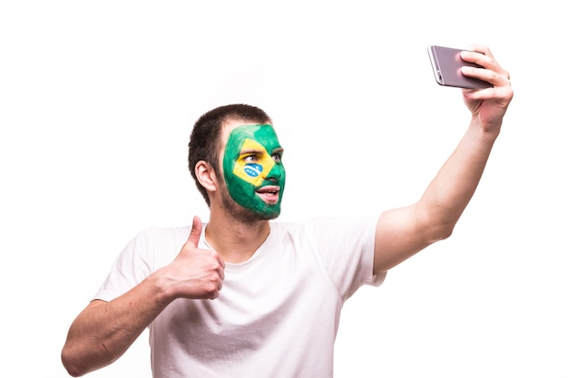 Fan support of brazil national team take selfie on the phone with painted face isolated on white background