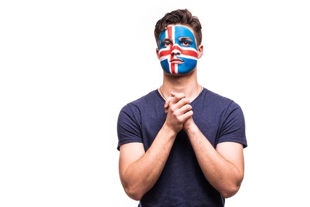 Il supporto dei fan della squadra nazionale islandese prega con la faccia dipinta isolata su priorità bassa bianca